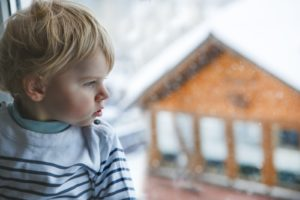 Little Toddler Boy Looking Out Of The Window On Winter Day With