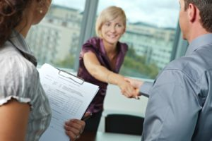Successful job interview - happy employee shaking hands, smiling