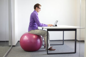 man on stability ball working with tablet - correct sitting posi