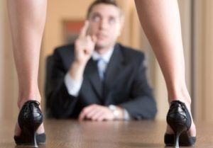 woman-standing-on-table-as-businessman-scolds-her